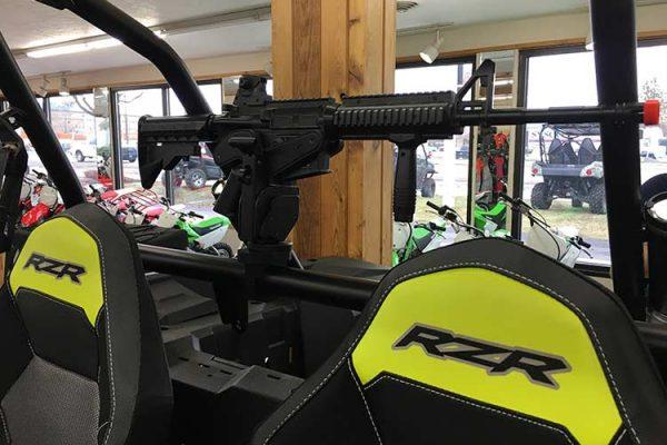 A replica AR-15 rifle is installed in a Polaris Razor with a Blac-Rac tube mount using a Blac-Rac 1070.
