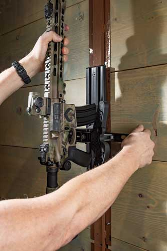 """A firearm owner unlocks an AR 15, releasing it from a Blac-Rac 1070 Weapon Retention System, wall mounted on an 18"""" T-channel."""