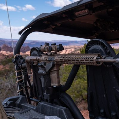1070 gun rack mounted to utility bars of yamaha utv holding ar15