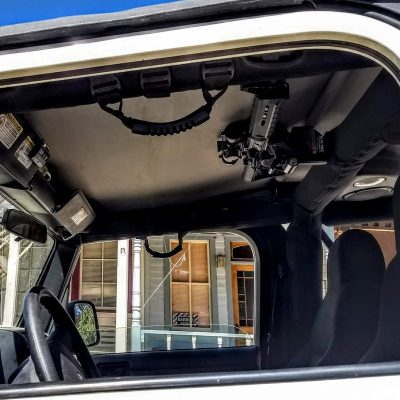 an overhead 1070 is mounted above the driver in a jeep using the jk mount holding an ar15