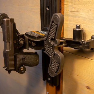 a wall mounted t-channel holding an opened 1070 gun rack with a sig handgun