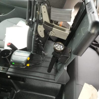 a freestand is mounted in a police cruiser to hold a 1082 gun rack and flashlight